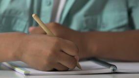 Colegial que hace la asignación casera, aprendiendo cómo escribir, práctica de la caligrafía almacen de video