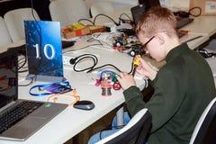 Colegial que hace un robot con el hierro de la soldadura eléctrica Foto de archivo