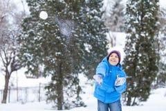 Colegial que juega bolas de nieve exteriores y que lanzan fotografía de archivo libre de regalías