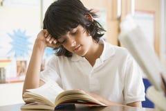 Colegial que lee un libro en clase Foto de archivo