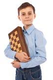 Colegial que lleva a cabo a una tarjeta de ajedrez Fotografía de archivo