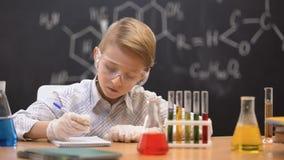 Colegial que mira el sedimento en frasco y que escribe los resultados, lección de la química almacen de video