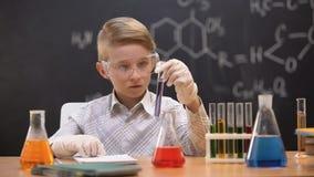 Colegial que mira la sustancia química en el tubo de ensayo, lección de la química, afición almacen de metraje de vídeo