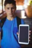 Colegial que se coloca con la cartera que muestra el teléfono móvil cerca de escalera en la escuela Imágenes de archivo libres de regalías