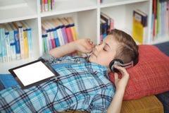 Colegial que se relaja en el sofá mientras que música que escucha en la tableta digital en biblioteca Foto de archivo libre de regalías
