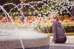 Colegial que se sienta cerca de la fuente en el parque de la ciudad Foto de archivo
