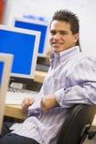 Colegial que se sienta delante de un ordenador Fotos de archivo libres de regalías