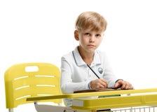 Colegial que se sienta en el escritorio Fotos de archivo