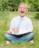 Colegial que se sienta en el parque con un cuaderno y risas Fotografía de archivo