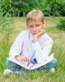 Colegial que se sienta en el parque con un trastorno del cuaderno Imagenes de archivo