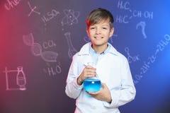 Colegial que sostiene el frasco de Florencia contra la pizarra con fórmulas escritas de la química fotografía de archivo