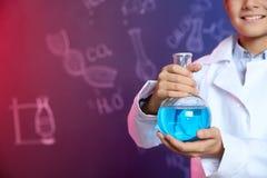 Colegial que sostiene el frasco de Florencia contra la pizarra con fórmulas escritas de la química, primer imagen de archivo libre de regalías