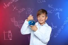 Colegial que sostiene el frasco de Florencia contra la pizarra con fórmulas de la química fotos de archivo