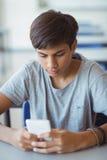 Colegial que usa el teléfono móvil en sala de clase Fotos de archivo