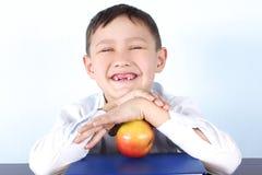 Colegial sin varios diente con la manzana Imagen de archivo