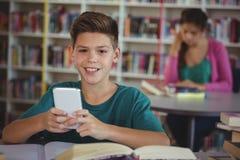 Colegial sonriente que usa el teléfono móvil en biblioteca en la escuela Foto de archivo libre de regalías