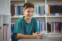 Colegial sonriente que usa el teléfono móvil en biblioteca en la escuela Imagen de archivo libre de regalías