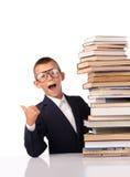 Colegial sorprendido con la pila enorme de libros Imagen de archivo