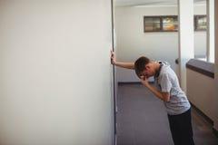 Colegial triste que se inclina contra la pared en pasillo Foto de archivo libre de regalías