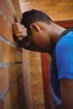 Colegial triste que se inclina en la pared de ladrillo Foto de archivo