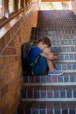Colegial triste que se sienta solamente en escalera Fotografía de archivo libre de regalías