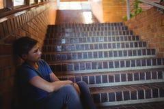 Colegial triste que se sienta solamente en escalera Foto de archivo libre de regalías