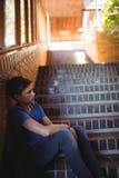 Colegial triste que se sienta solamente en escalera Fotos de archivo