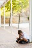 Colegial triste que se sienta solamente en pasillo Foto de archivo libre de regalías