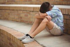 Colegial triste que se sienta solamente en pasos en campus Imagen de archivo libre de regalías
