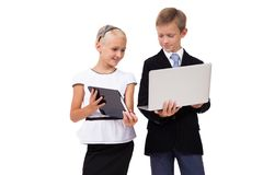 Colegial y colegiala con un ordenador portátil con una tableta en un blanco Imagen de archivo libre de regalías