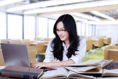 Colegiala adolescente atractiva que mecanografía en el ordenador portátil Fotografía de archivo libre de regalías