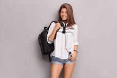 Colegiala adolescente con los auriculares que llevan una mochila Imágenes de archivo libres de regalías