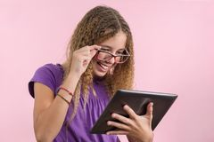 Colegiala adolescente con los vidrios usando la tableta digital Foto de archivo libre de regalías