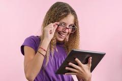 Colegiala adolescente con los vidrios usando un ordenador portátil Foto de archivo