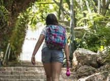 Colegiala adolescente con una mochila en su detrás y los auriculares Foto de archivo
