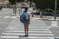 Colegiala adolescente con una mochila en su detrás y los auriculares Imagen de archivo