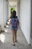 Colegiala adolescente con una mochila en su detrás y los auriculares Fotografía de archivo libre de regalías