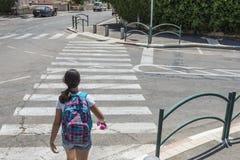 Colegiala adolescente con una mochila en su detrás y los auriculares Fotografía de archivo
