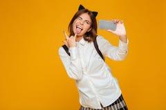 Colegiala adolescente divertida en uniforme con la mochila Imagen de archivo libre de regalías