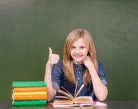 Colegiala adolescente en la sala de clase que muestra el pulgar para arriba Imagenes de archivo