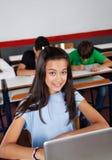 Colegiala adolescente feliz que se sienta con el ordenador portátil en Fotografía de archivo