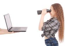 Colegiala adolescente feliz que usa los prismáticos que miran la pantalla del ordenador portátil Foto de archivo