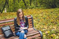 Colegiala adolescente hermosa que estudia en un parque Imagen de archivo libre de regalías