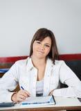 Colegiala adolescente hermosa que se sienta en el escritorio Fotografía de archivo