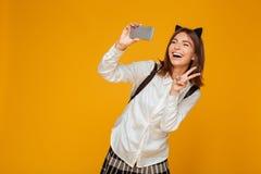 Colegiala adolescente joven en uniforme con la mochila Imagen de archivo libre de regalías