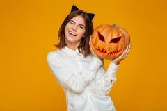 Colegiala adolescente linda en la calabaza uniforme de Halloween que se sostiene Imagen de archivo libre de regalías