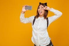 Colegiala adolescente loca en uniforme con la mochila Imagen de archivo libre de regalías