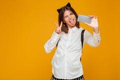 Colegiala adolescente loca en uniforme con la mochila Imagenes de archivo
