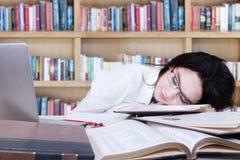Colegiala adolescente que duerme en biblioteca Imagenes de archivo