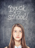 Colegiala adolescente que mira para arriba en el fondo de la pizarra Fotografía de archivo